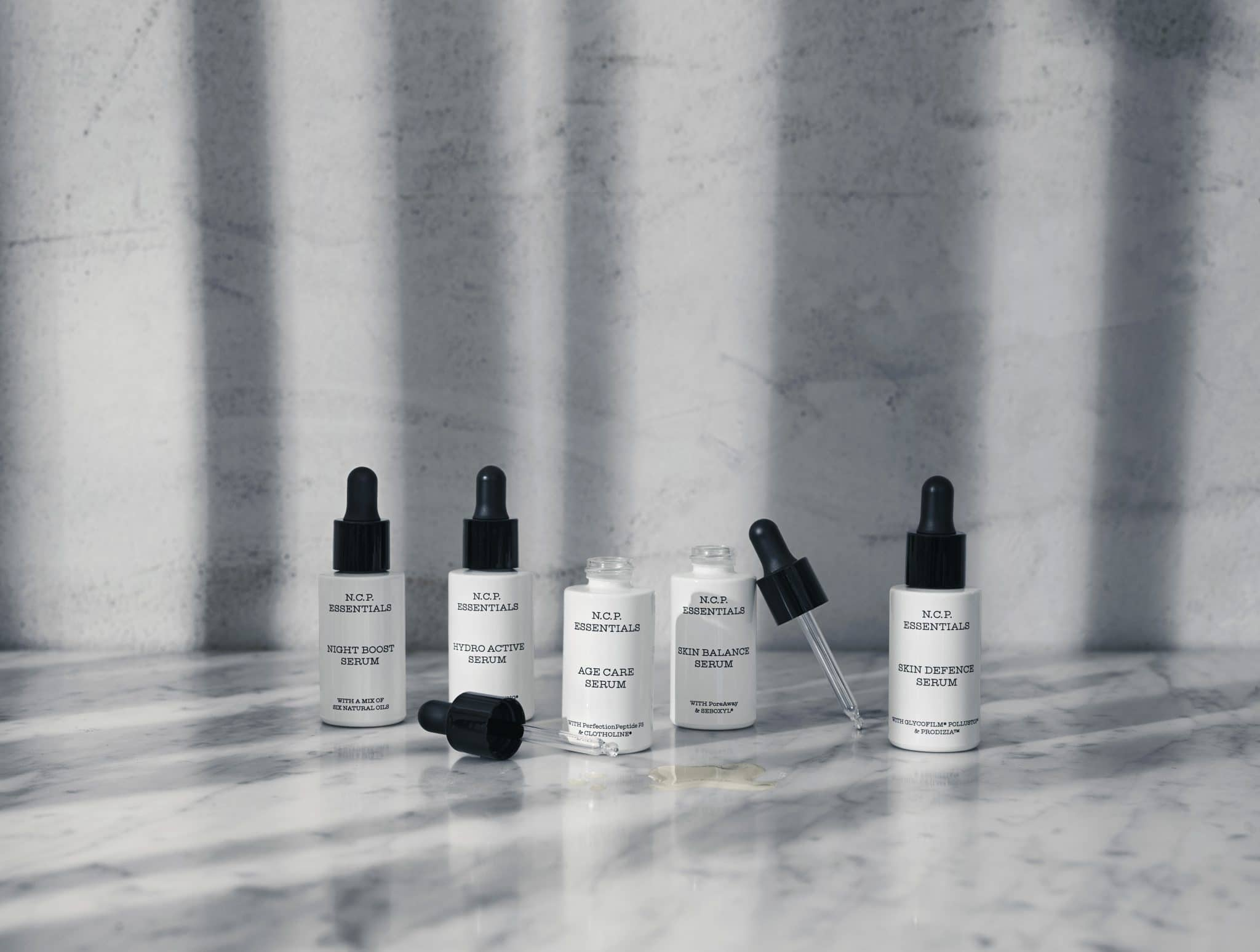 Vegan skin care from N.C.P Essentials. The boost line of Skin care on marbel table. Age Care Serum and Skin Balance Serum is open and showing the pipette.Age Care Serum, Hydro Active Serum, Night Boost Serum, Skin Balance Serum & Skin Defence Serum