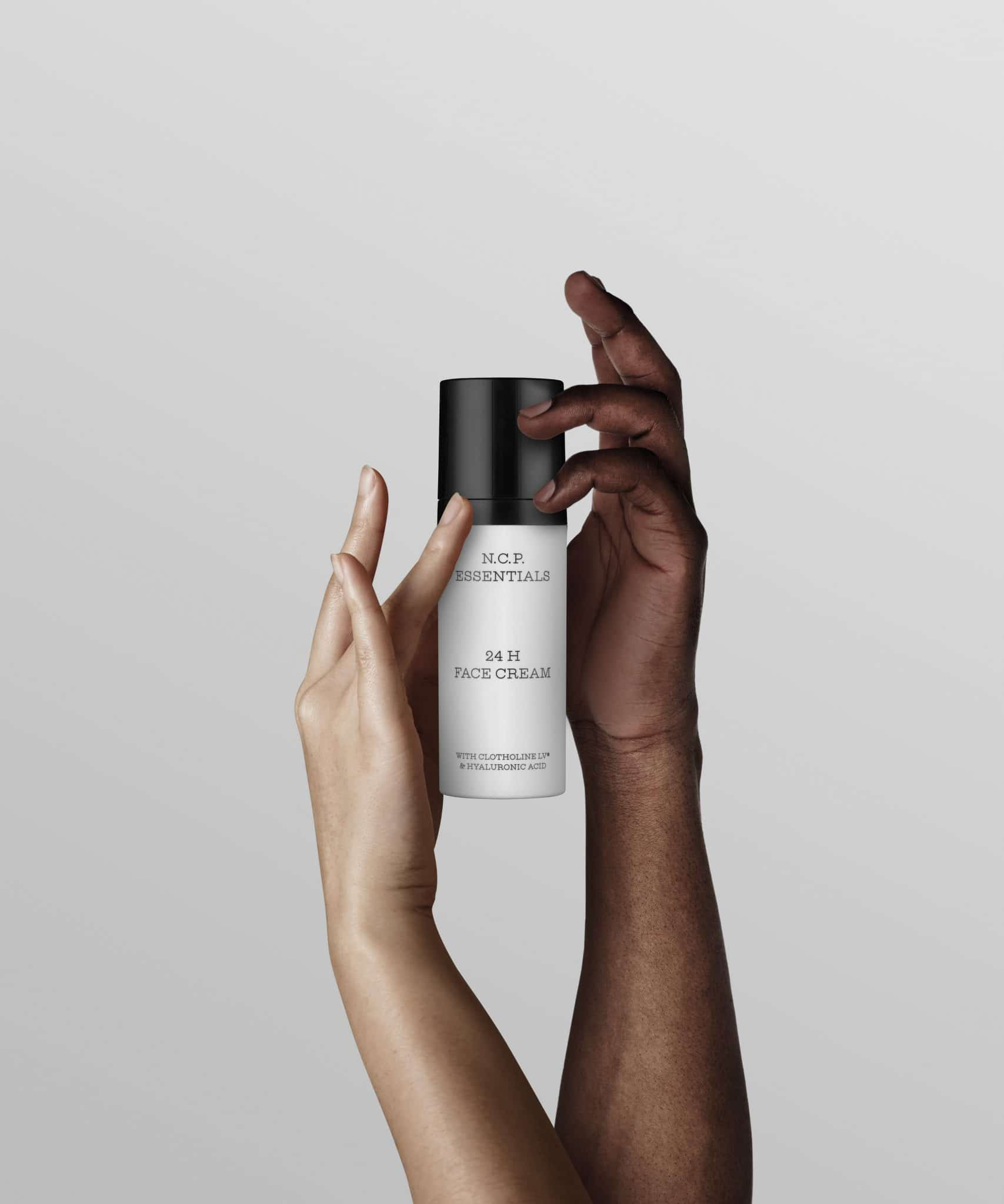 Day and night cream from N.C.P with one white and one black hand holding the product. A withe bottle with black text and a black cap. 24 H Face Cream.