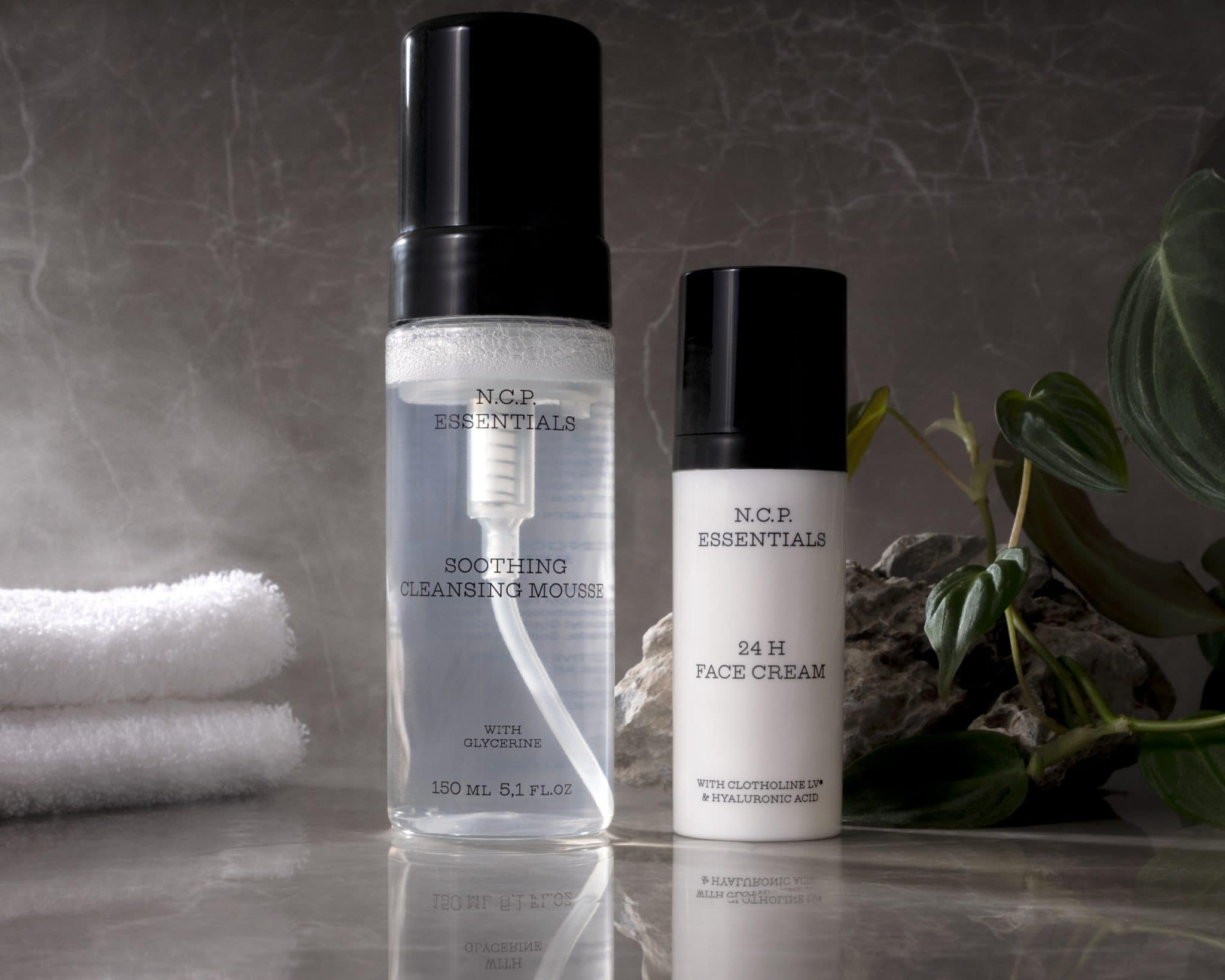 Vegan & fragrance free skincare from N.C.P. Clean & Care kit with Soothing Cleansing Mousse a transparent bottle with a black cap and 24 H Face Cream a white bottle with black text and black cap.White towel and green leafs