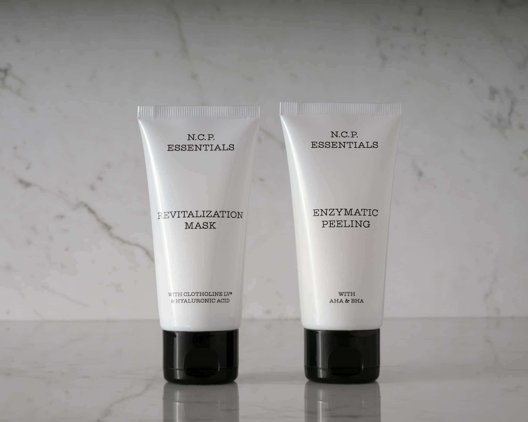 Vegan & fragrance free skincare from N.C.P. Glowing kit with Revitalization Mask a white bottle with black text and black cap & Enzymatic Peeling a white bottle with black text and black cap. Picture is black and white with marble background.