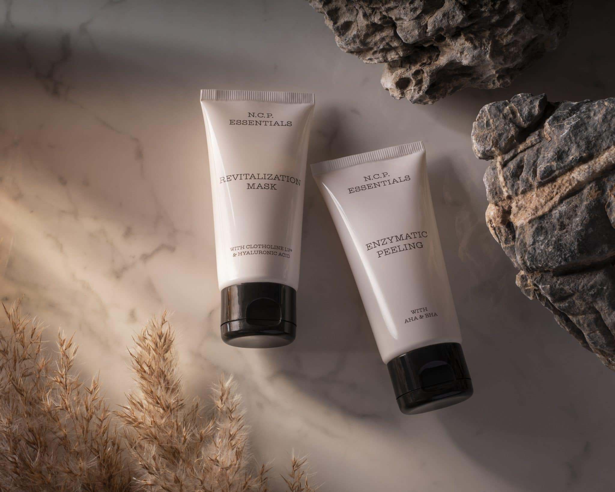 Vegan & fragrance free skincare from N.C.P. Glowing kit with Revitalization Mask a white bottle with black text and black cap & Enzymatic Peeling a white bottle with black text and black cap. Products laying down on a marble background. Stone and dry grass.