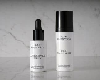 Vegan & fragrance free skincare from N.C.P. Hydration kit with 24 H Face Cream a white bottle with black text and black cap & Hydro Active Serum a white bottle with black text and black pipette. Picture is black and white with a marble background.